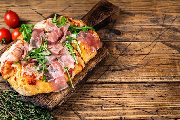 Gesneden pizza met prosciutto, parmaham, rucola en parmezaanse kaas op een houten bord. houten achtergrond. bovenaanzicht. kopieer ruimte.