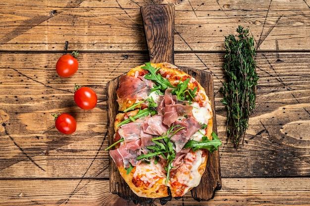 Gesneden pizza met prosciutto, parmaham, rucola en parmezaanse kaas op een houten bord. houten achtergrond. bovenaanzicht.