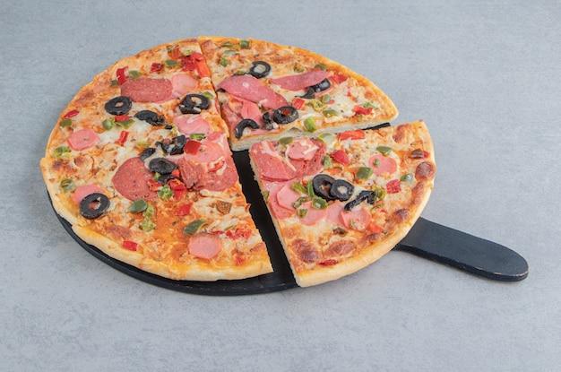 Gesneden pizza op een zwart bord op marmer
