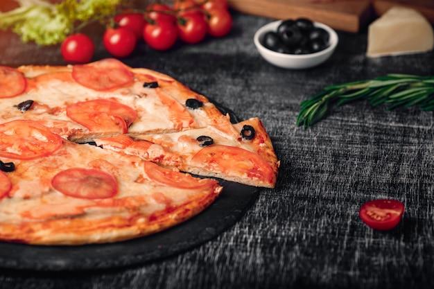 Gesneden plakje pizza met kaas, forel, tomaten, olijven en garnalen op schoolbord.
