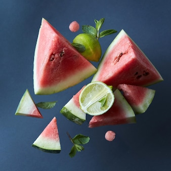 Gesneden plakjes watermeloen geïsoleerd op een zwarte ondergrond met limoenen en bladeren