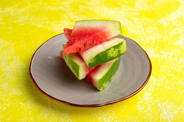 Gesneden plakkerige watermeloen in plaat op geel