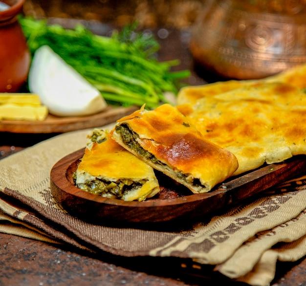 Gesneden plantaardige brood op een rustieke plaat op een houten tafel met kruiden en ui