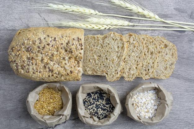Gesneden plat brood met weath, haver en zaad op papieren zakken