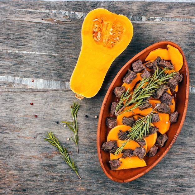 Gesneden pompoen gebakken met vlees in een klei pot. herfstmaaltijd met rozemarijn en kruiden