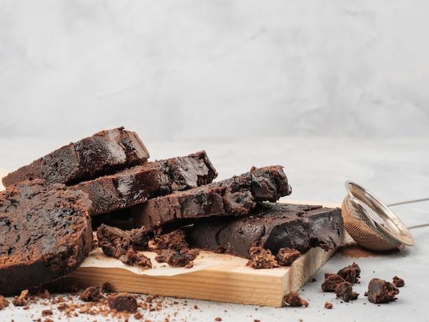 Gesneden pond chocoladetaart staat op wit met chocoladeschilfers en cacao.