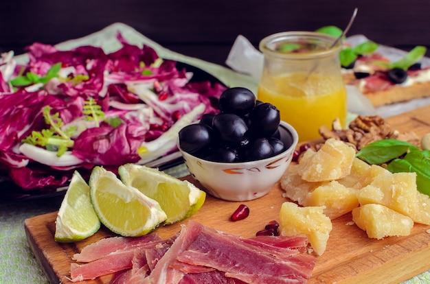 Gesneden prosciutto met salade en olijfolie