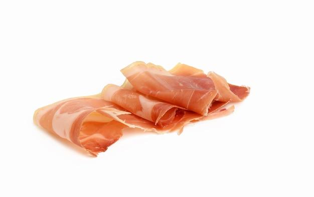 Gesneden prosciutto schokkerig in dunne plakjes, voedsel geïsoleerd op een witte achtergrond