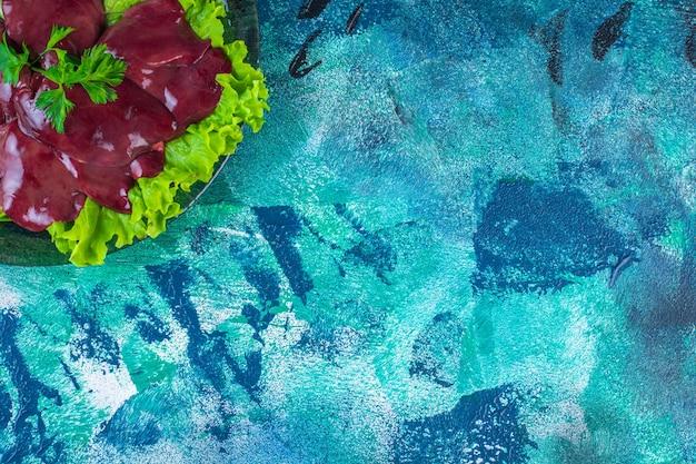 Gesneden radijs en slachtafval op een slablad op de plaat, op de blauwe achtergrond
