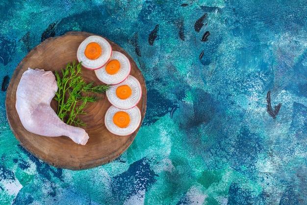 Gesneden radijs en wortelen met dille en kippendrumstick op een plank