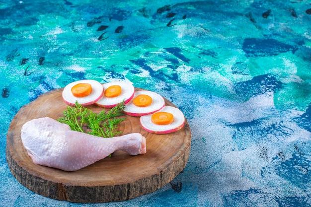 Gesneden radijs en worteltjes met dille en kipdrumstick op een bord