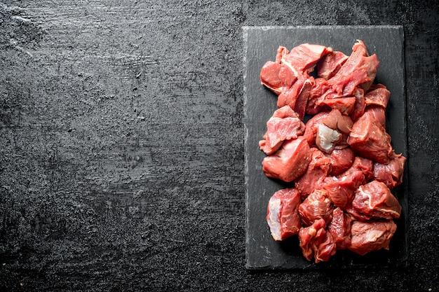 Gesneden rauw rundvlees op een stenen bord. op zwarte rustieke achtergrond