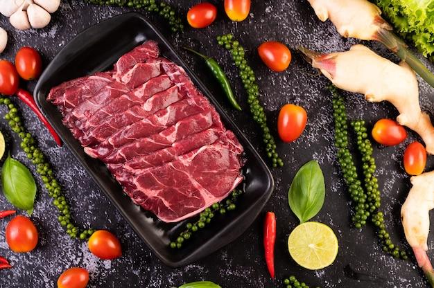 Gesneden rauw varkensvlees gebruikt voor het koken met chili, tomaat, basilicum en verse peperzaden.