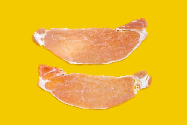 Gesneden rauw varkensvlees op gele achtergrond.