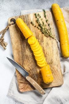 Gesneden rauwe gele biologische wortelen op een snijplank