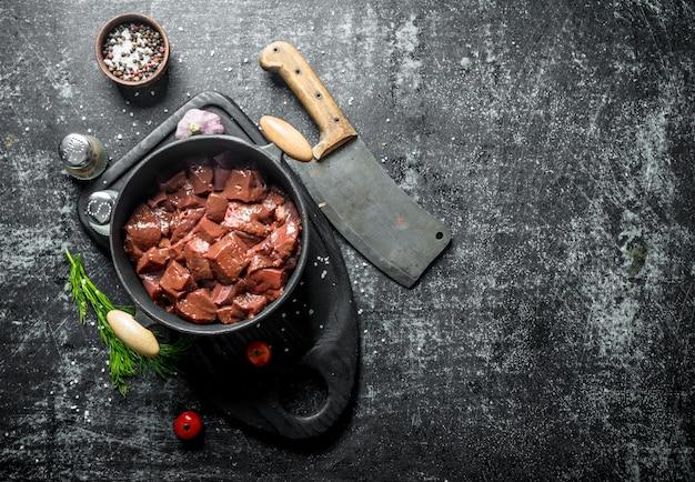 Gesneden rauwe lever in een pan met mes, kruiden en dille. op donkere rustieke ondergrond