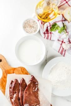 Gesneden rauwe runderlever met ingrediënten voor het koken