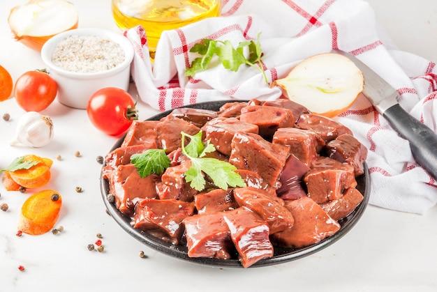 Gesneden rauwe runderlever met specerijen, kruiden en groenten, witte marmeren tafel