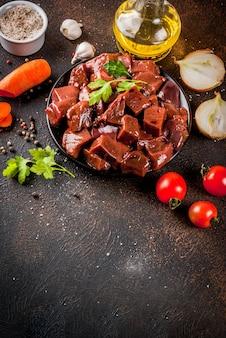Gesneden rauwe runderlever met specerijen, kruiden en groenten