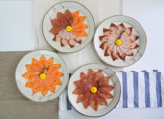 Gesneden rauwe zalm, hamachi, maguro-sashimi op keramische schotel
