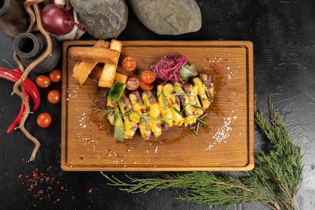 Gesneden rib eye steak met kaassaus, groenten en tarwecroutons