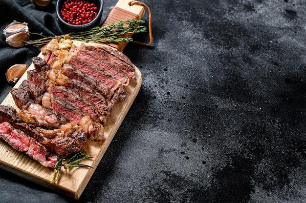 Gesneden rib eye steak op een snijplank, medium rood. bovenaanzicht. kopieer ruimte
