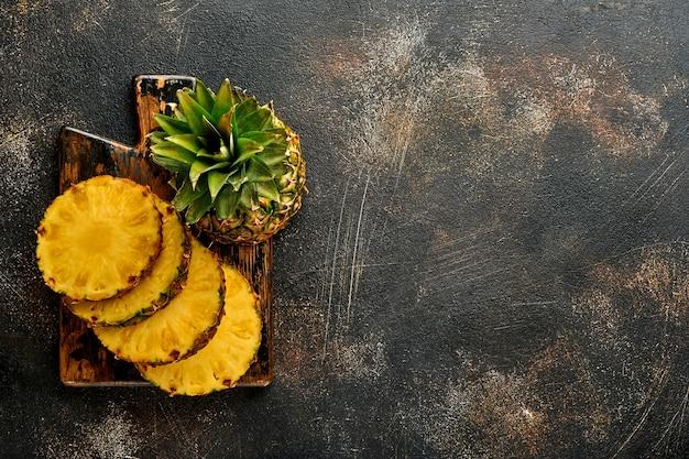 Gesneden rijpe ananas op donkere bruine stenen achtergrond. tropische vruchten. bovenaanzicht. vrije ruimte voor tekst.