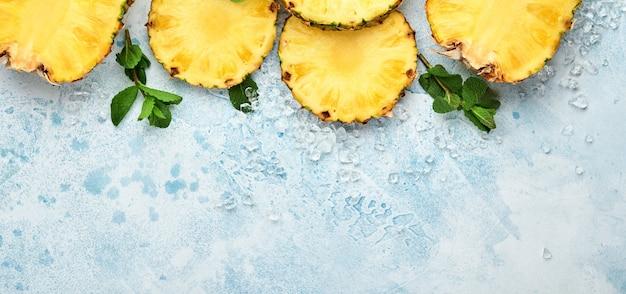 Gesneden rijpe ananas op lichtblauwe stenen achtergrond. tropische vruchten. bovenaanzicht. vrije ruimte voor tekst.