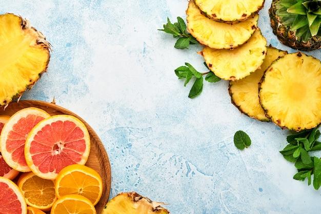 Gesneden rijpe ananas, sinaasappel en grapefruit op lichtblauwe stenen achtergrond. tropische vruchten. bovenaanzicht. vrije ruimte voor tekst.