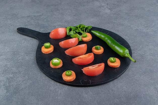 Gesneden rijpe groenten op zwarte snijplank.