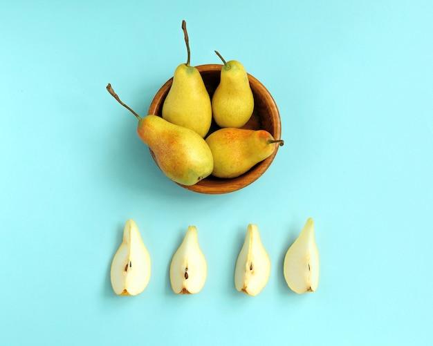 Gesneden rijpe peer op een plaat en hele peren op blauw