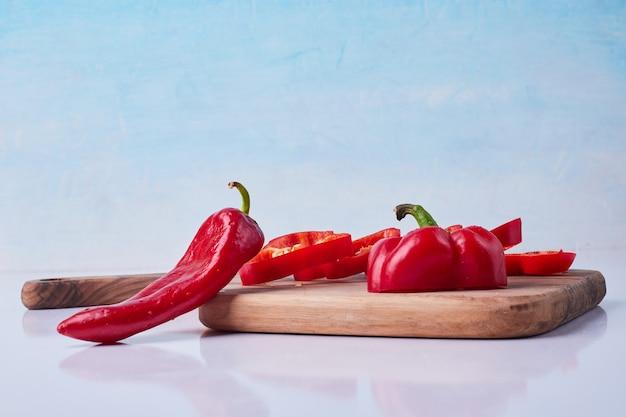 Gesneden rode chili en paprika op een houten schotel op blauw.