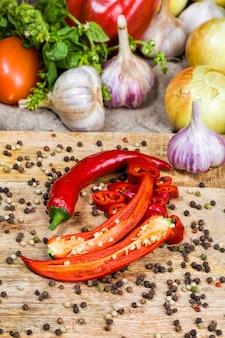 Gesneden rode hete pepers. uien. hele knoflook en andere groenten tijdens het koken