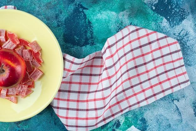 Gesneden rode marmelade en appel in een bord op theedoek, op de blauwe tafel.