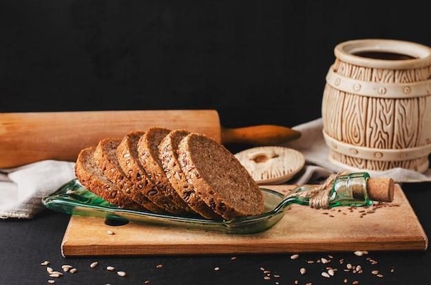 Gesneden rogge volkoren brood met zonnebloempitten, vlas of linnen zaad en sesam op een bord gemaakt van een fles