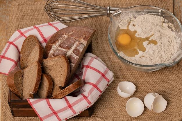 Gesneden roggebrood en bloem met eieren.