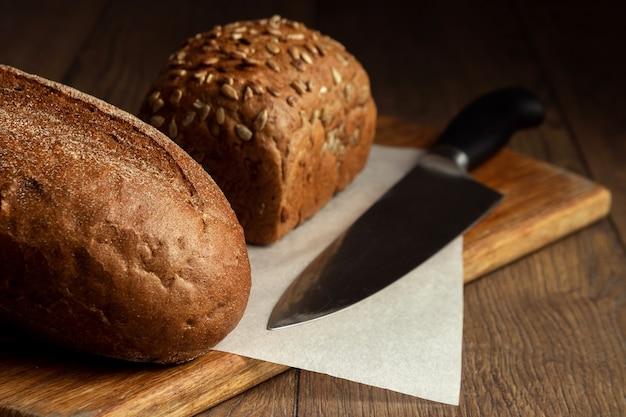 Gesneden roggebrood en een messenclose-up, op een houten snijplank
