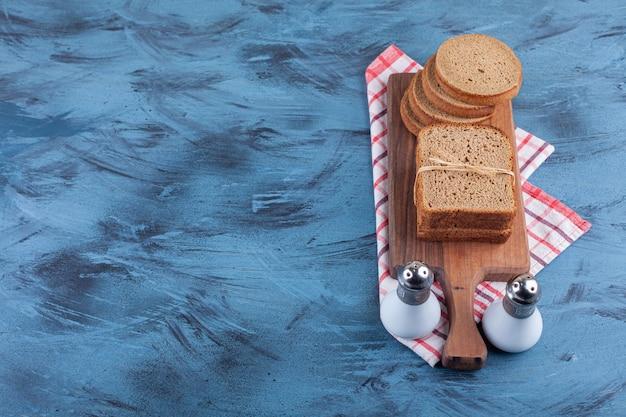 Gesneden roggebrood op een bord op handdoek, op het blauw.