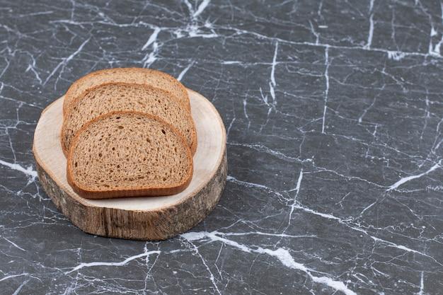 Gesneden roggebrood op een houten bord over grijs.