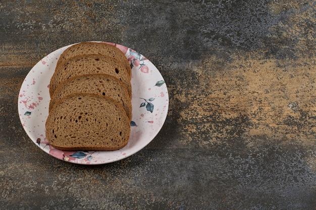 Gesneden roggebrood op kleurrijke plaat