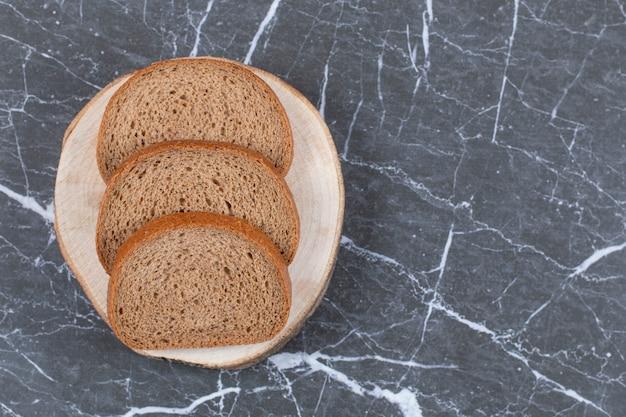 Gesneden roggebrood op snijplank over grijs.