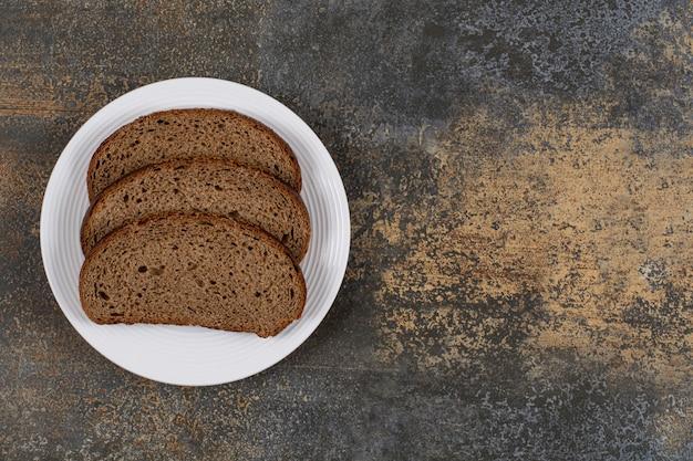 Gesneden roggebrood op witte plaat