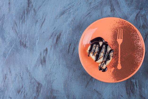 Gesneden roltaart versierd met chocoladesiroop op oranje plaat.
