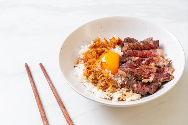 Gesneden rundvlees op gegarneerde rijstkom met ei