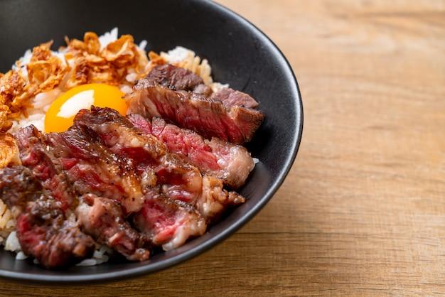 Gesneden rundvlees op gegarneerde rijstkom met ei Premium Foto
