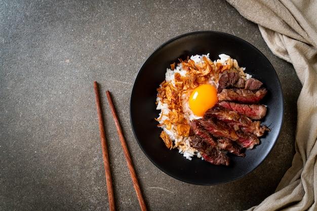 Gesneden rundvlees op rijstkom met ei Premium Foto