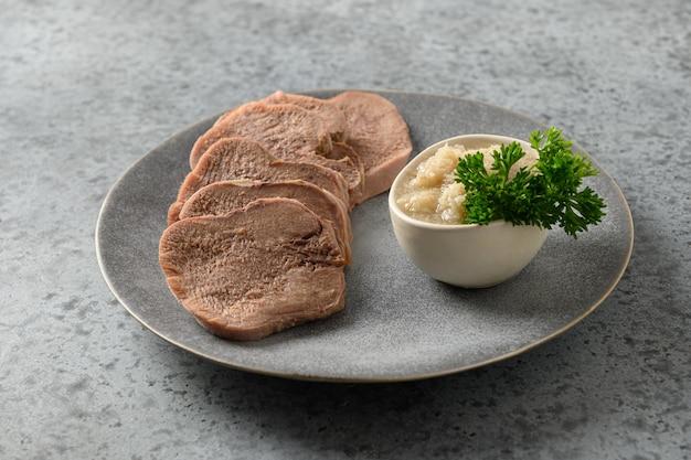 Gesneden rundvleestong met mierikswortelsaus op grijs