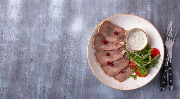 Gesneden rundvleestong op een plaat die met mes en vork wordt gediend. bovenaanzicht,