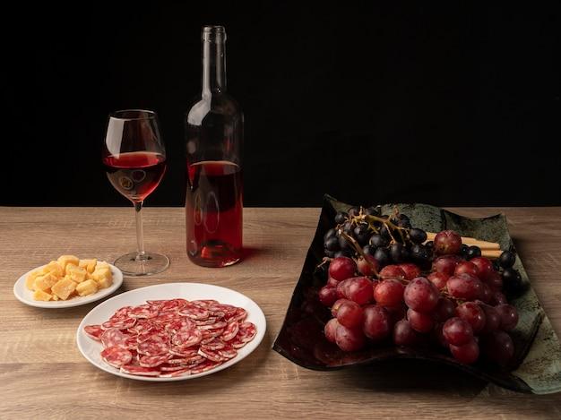 Gesneden salami en kaas met rode wijn, twee soorten druiven en italiaanse grissini