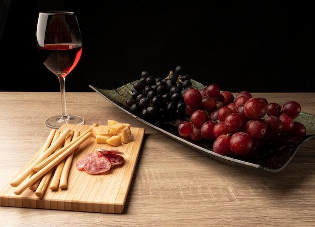 Gesneden salami en kaas met rode wijn